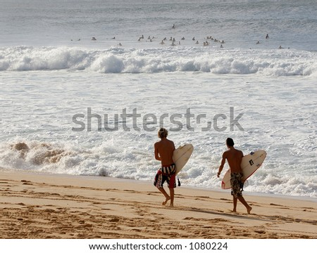 Surfers at Bonzai Pipeline off of Oahu's North Shore. - stock photo