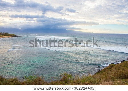 Surfers bay near the island of Maui, Hawaii during sunset time with an islands on the background and surfers in the water catching waves. - stock photo