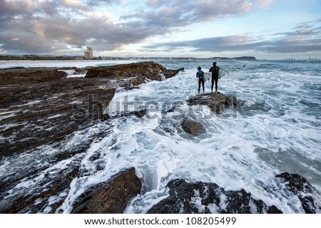Surfers catching a wave from rocks, Elephant Rock, Currumbin beach, Gold Coast, Australia - stock photo