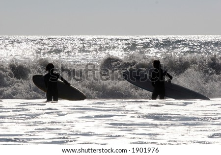 Surfers in the waves. - stock photo