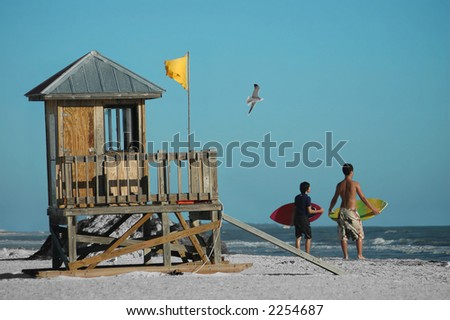 Surfers infront of a watch tower by the beach - stock photo