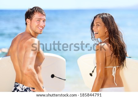 Surfers on beach having fun in summer. Surfer woman and man with boogieboard smiling happy on beach on Hawaii. Multiracial couple Asian woman and Caucasian man in outdoor water activity during travel. - stock photo