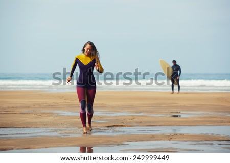 Surfers on beautiful beach, surfer girl going back to the beach while her friend wait big waves holding surfboard - stock photo