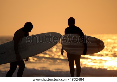 Surfers on the beach at sunset - stock photo