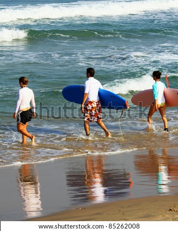 Surfers on the way to the sea - stock photo