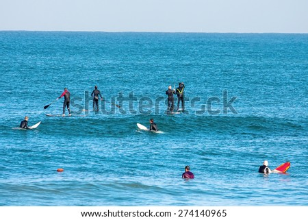 Surfers on the way to the sea waiting for waves - stock photo