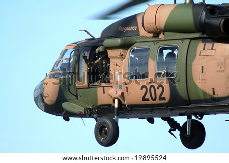 SURFERS PARADISE, Australia - October 26, 2008: Australian Army Blackhawk flies by with soldier giving thumbs up at the Indy 300, Surfers Paradise, Australia. - stock photo