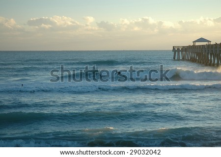 Surfers riding ocean waves, next to pier, early morning sun - stock photo