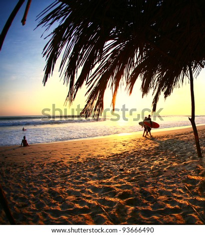 Surfers Walk Home at Sunset Along Ocean in Costa Rica - stock photo