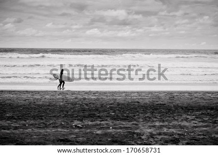 Surfers walking along the beach - stock photo