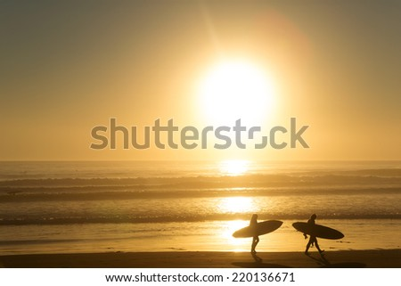 surfers walking on the beach with the setting sun over the water in the background - stock photo