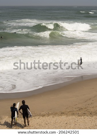 surfers watching the waves and surfing - stock photo