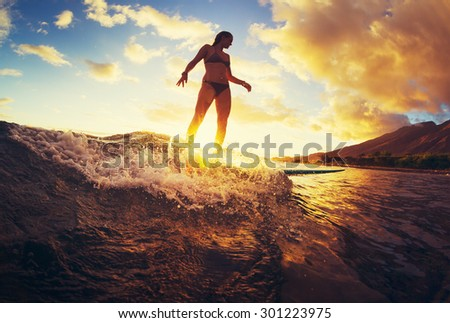 Surfing at Sunset. Beautiful Young Woman Riding Wave at Sunset. Outdoor Active Lifestyle. - stock photo