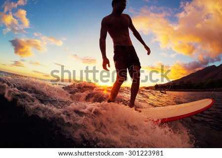 Surfing at Sunset. Young Man Riding Wave at Sunset. Outdoor Active Lifestyle. - stock photo