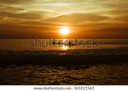 Surfing at Sunset. Young Man Riding Wave at Sunset. Outdoor Active Lifestyle