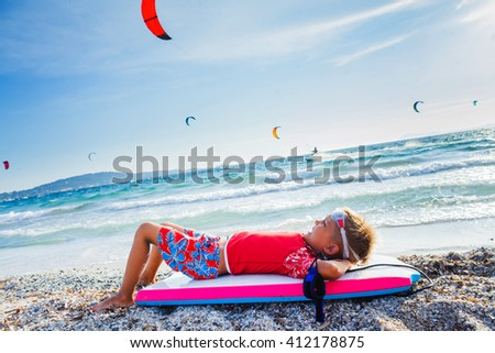 Surfing boy on a beach looking on the sea and dreaming of kite-surf. Sunset time. - stock photo