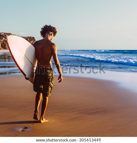 Surfing. Freedom. Life. Handsome Surfer stay on the Beach - stock photo