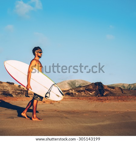Surfing. Freedom. Travels. Extreme. Surfer on the Beach with Board