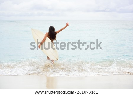 Surfing girl happy excited going surfing at ocean beach running into water. Female bikini woman heading for waves with surfboard having fun living healthy active lifestyle by sea. Water sports model. - stock photo