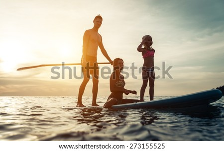surfing. happy family silhouette on the paddle board. concept about family, sport and fun - stock photo