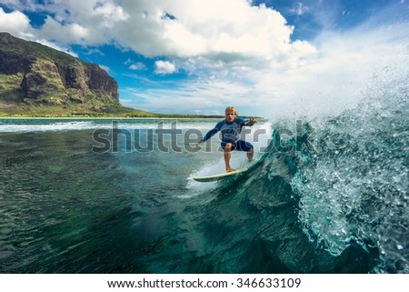 surfing in Mauritius. muscular surfer with long white hair riding on big waves on the Indian Ocean island of Mauritius - stock photo