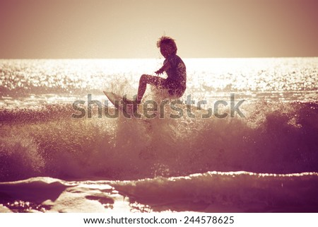Surfing in the early morning with retro effect applied. - stock photo