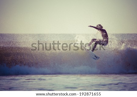 Surfing in the early morning with vintage effect applied. - stock photo