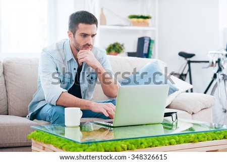 Surfing net at home. Handsome young man working on laptop while sitting on the couch at home  - stock photo