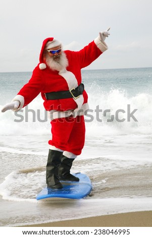 Surfing Santa Claus. Santa Claus rides on his surfboard as he rides the waves of the ocean blue. Santa Loves Sports the beach and the outdoors. Santa loves to surf on his surfboard as much as he can - stock photo