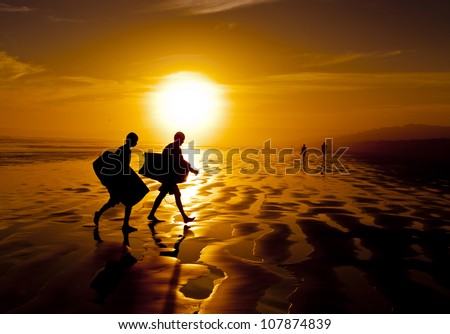Surfing Sunset. Silhouette of two surfers carrying boogie boards along the sand of a beach. - stock photo