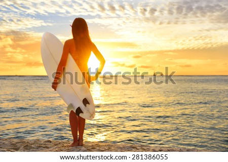 Surfing surfer girl looking at ocean beach sunset. Silhouette of female bikini woman looking at water with standing with surfboard having fun living healthy active lifestyle. Water sports with model. - stock photo