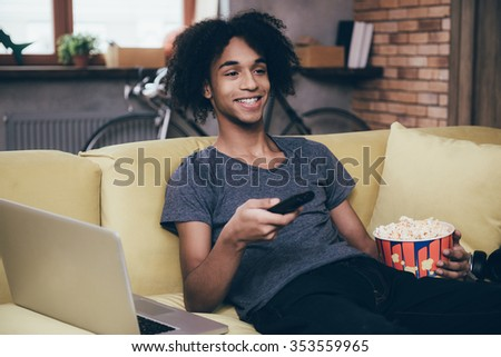 Surfing the channels. Cheerful young African man watching TV and holding remote control while sitting with bucket of popcorn on the couch at home - stock photo