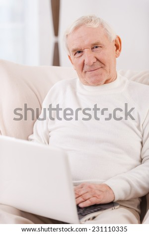 Surfing the net. Confident senior man working on laptop and looking at camera while sitting in chair at his apartment - stock photo