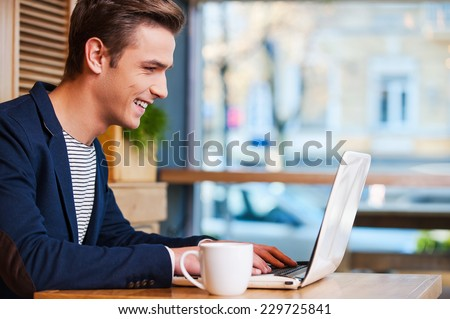 Surfing the net in cafe. Side view of handsome young man working on laptop and smiling while enjoying coffee in cafe - stock photo