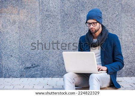 Surfing the net outdoors. Handsome young man in smart casual wear working on laptop while sitting outdoors - stock photo