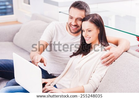 Surfing the net together. Beautiful young loving couple bonding to each other and looking at the laptop with smile while sitting on the couch together  - stock photo