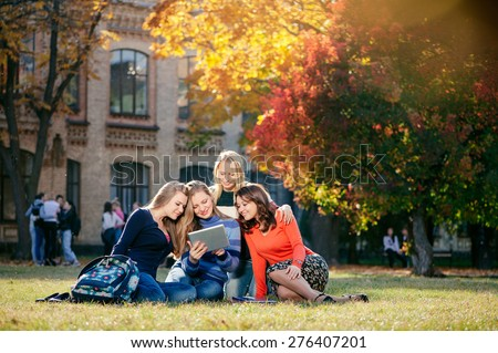 Surfing the net together. Four happy attractive female caucasian students looking at tablet pc and smiling while  sitting on grass at campus together - stock photo