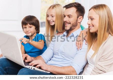 Surfing the net together. Side view of happy family of four bonding to each other and smiling while surfing the net at their laptop - stock photo