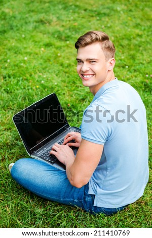 Surfing the net wherever I want. Top view of happy young man looking over shoulder and smiling while sitting on the grass with laptop