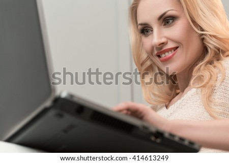 Surfing the network. Shot of an attractive woman sitting on a sofa using a laptop.  - stock photo