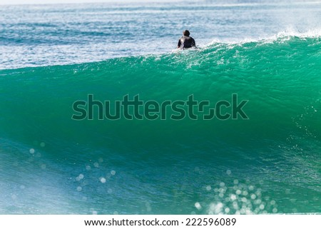 Surfing Unidentified Wave Surfing surfer paddles over large ocean wave - stock photo