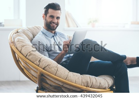 Surfing web from his tablet. Confident young handsome man working on digital tablet and smiling while sitting in big comfortable chair at home   - stock photo