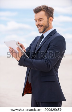 Surfing web in desert. Confident young man in formalwear working on digital tablet and smiling while standing in desert - stock photo