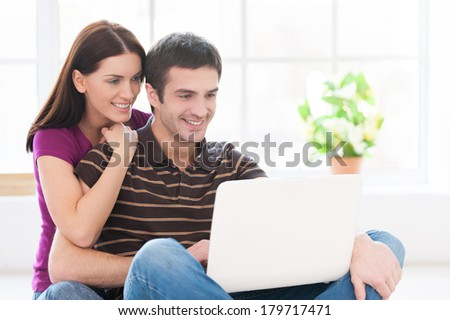 Surfing web is fun. Cheerful young couple working on laptop together while sitting on the floor at their apartment - stock photo