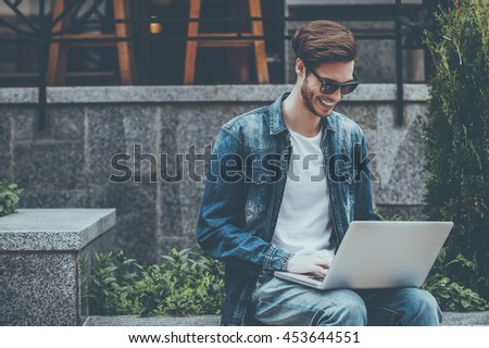 Surfing web outdoors. Smiling young man working on laptop while sitting outdoors - stock photo