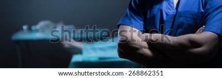 Surgeon guilty of patient's death standing with crossed arms - stock photo