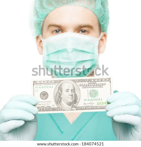 Surgeon holding dollar bill in his hands isolated on white background - 1 to 1 ratio - stock photo