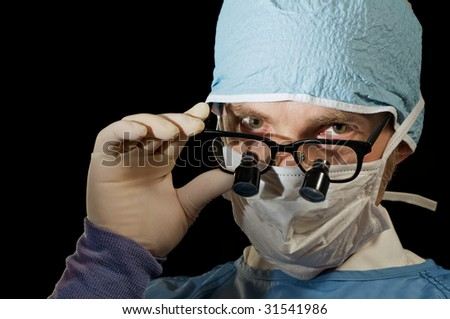 Surgeon looks over magnifying glasses - stock photo