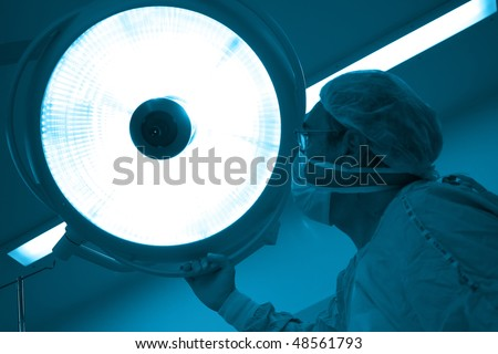 Surgeon moving the surgical reflector at the  operating room - stock photo