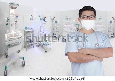 surgeon pose arms crossed behind back in aided the recovery room with newborn in incubator at hospital  - stock photo